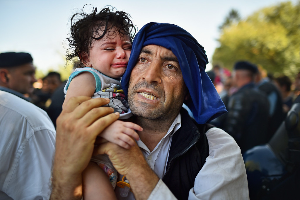 . A man holds his crying child close to him as migrants force their way through police lines at Tovarnik station for a train to take them to Zagreb on September 17, 2015 in Tovarnik, Croatia. Migrants are crossing into Croatia from Serbia two days after Hungary sealed its border with Serbia, the majority of them want to reach Germany, amid divisions within the European Union over how to manage the ongoing crisis.  (Photo by Jeff J Mitchell/Getty Images)