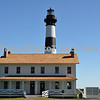 The current Bodie Island Lighthouse is the third that has stood in this vicinity of Bodie Island on the Outer Banks in North Carolina and was built in 1872. It stands 156 feet tall and is located on the Roanoke Sound side of the first island that is part of the Cape Hatteras National Seashore. The lighthouse is just south of Nags Head, a few miles before Oregon Inlet.<br /> <br /> BODIE ISLAND LIGHT FACTS:<br /> <br /> 1847 - The contractor on the first project was Mr. Francis Gibbons, of Baltimore, who would later become a prominent lighthouse builder on the West Coast. Cost was $5,000 but problems with location and design of the tower caused a ten year delay in construction. The tower was highly unstable and soon after it was completed, it began to lean toward the sea.<br /> 1859 - The Bodie Island Lighthouse had deteriorated and the Lighthouse Board secured a $25,000 appropriation from Congress to erect a new tower. This new tower was 80 ft (24 m). and its lantern was a third-order Fresnel lens.<br /> 1861 - In the fall of 1861, Confederate troops stacked explosives inside the tower and blew it apart.<br /> 1871 - A third lighthouse was completed in 1871 partially with material left over from construction of a new tower at Cape Hatteras. The tower was 156 ft (48 m). with a first order Fresnel lens that made its light visible for 18 nautical miles (33 km). The Bodie tower is painted with white and black horizontal bands.
