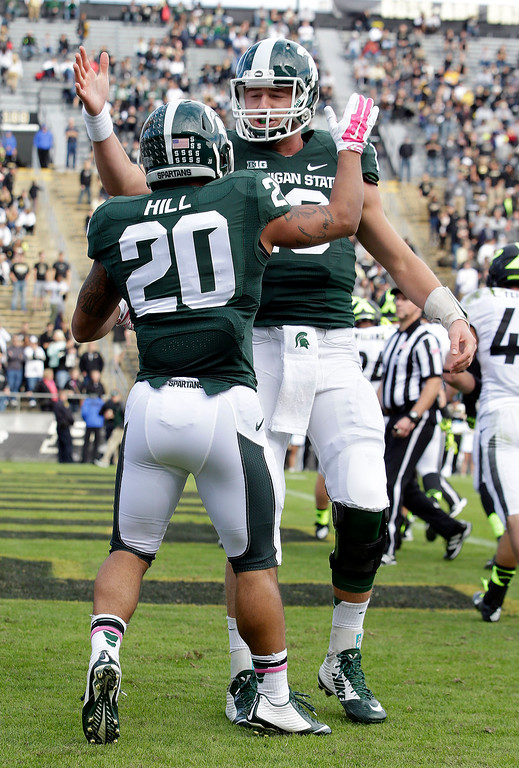 . Michigan State quarterback Connor Cook, right, congratulates Michigan State running back Nick Hill (20) on a touchdown during the first quarter against Purdue in an NCAA college football game in West Lafayette, Ind., Saturday, Oct. 11, 2014. (AP Photo/AJ Mast)