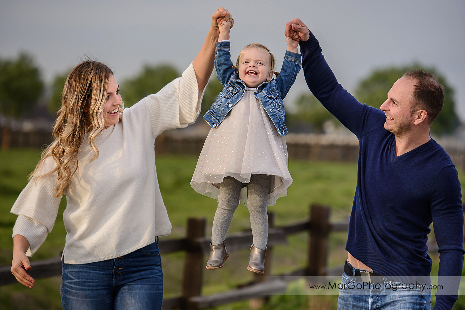 mother and father wearing white and navy blue clothes lifting little girl in white dress during family session at San Jose Martial Cottle Park