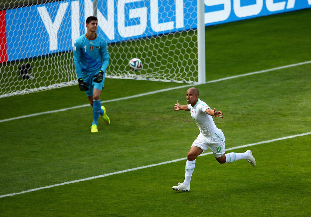 . BELO HORIZONTE, BRAZIL - JUNE 17: Sofiane Feghouli of Algeria celebrates scoring his team\'s first goal on a penalty kick past Thibaut Courtois of Belgium during the 2014 FIFA World Cup Brazil Group H match between Belgium and Algeria at Estadio Mineirao on June 17, 2014 in Belo Horizonte, Brazil.  (Photo by Quinn Rooney/Getty Images)