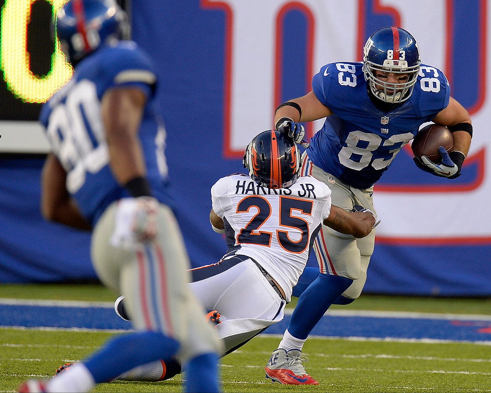 . New York Giants tight end Brandon Myers (83) stiff arms Denver Broncos cornerback Chris Harris (25) as he gains a few yards during the second quarter September 15, 2013 MetLife Stadium. (Photo by John Leyba/The Denver Post)
