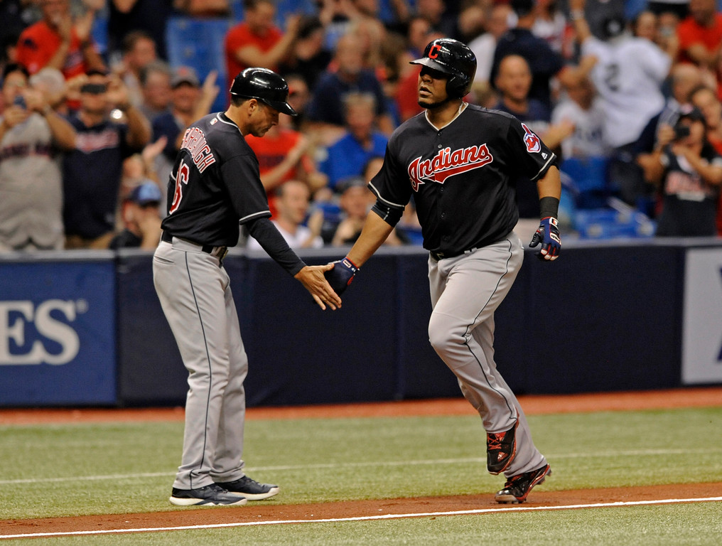 . Cleveland Indians third base coach Mike Sarbaugh, left, congratulates Edwin Encarnacion after his solo home run off Tampa Bay Rays starter Jake Faria during the fifth inning of a baseball game Friday, Aug. 11, 2017, in St. Petersburg, Fla. (AP Photo/Steve Nesius)