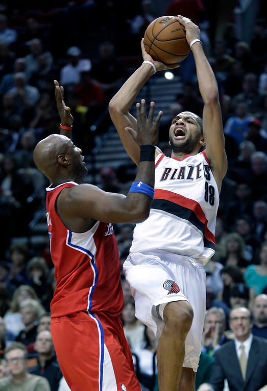 . Portland Trail Blazers forward Nicolas Batum, right, from France, shoots over Los Angeles Clippers forward Lamar Odom during the second half of an NBA basketball game in Portland, Ore., Saturday, Jan. 26, 2013.  Batum scored 20 points as the Trail Blazers defeated the Clippers 101-100. (AP Photo/Don Ryan)