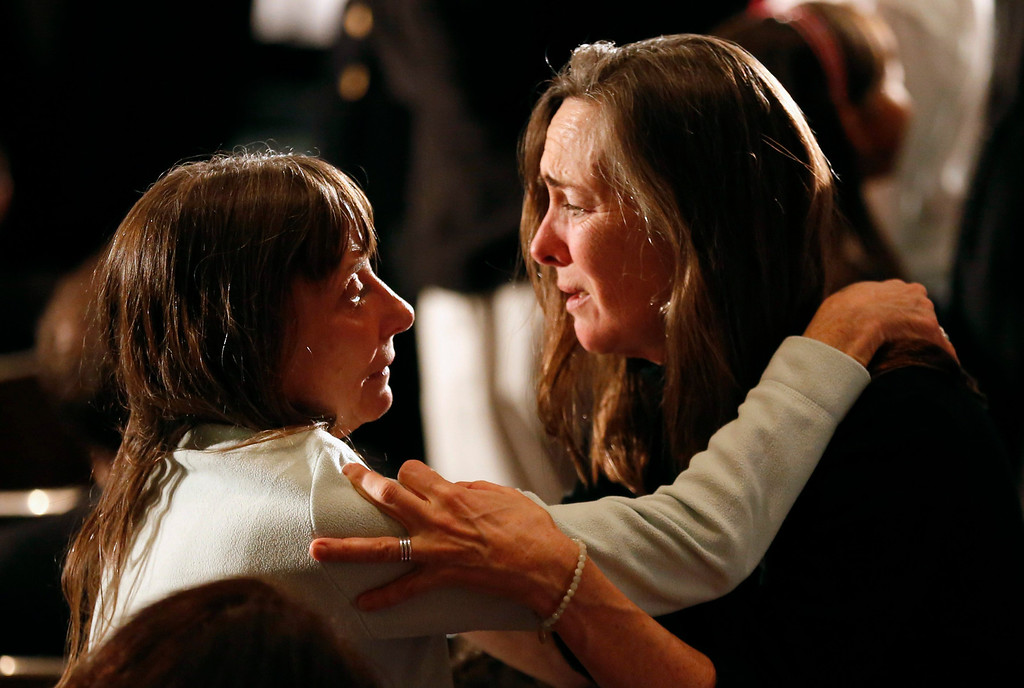 . Women comfort one another during a vigil held at Newtown High School for families of victims of the Sandy Hook Elementary School shooting in Newtown, Connecticut December 16, 2012. U.S. President Barack Obama is visiting Newtown High School to meet with the families of the victims and to thank first responders to the school shooting here, which was one of the deadliest such incidents in the nation\'s history. REUTERS/Kevin Lamarque
