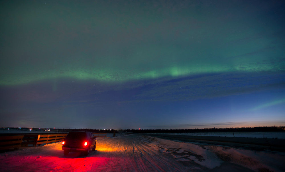Description of . The aurora borealis, or northern lights, fill the sky early Sunday, March 17, 2013, above a motorist stopped in a roadside scenic pullout in Kenai, Alaska. The bright display at times filled the sky. (AP Photo/M. Scott Moon)