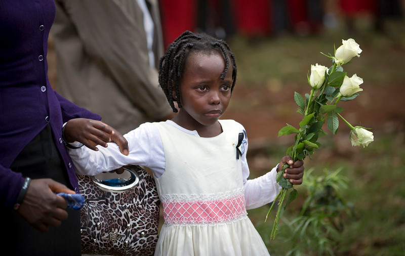 . Miriam, 6, is helped by a relative as she prepares to lay a bouquet of flowers for Christopher Chewa who was killed in the Westgate Mall attack, the father of her cousin Gloria, 4, as she and other families of the victims lay flowers and remember at the Amani Garden memorial site in the Karura Forest in Nairobi, Kenya Sunday, Sept. 21, 2014. Kenya is marking one year since four gunmen stormed the upscale Westgate Mall in Nairobi, killing 67 people, and a memorial plaque with the names of the victims was unveiled at the popular forest on the edge of the city. (AP Photo/Ben Curtis)
