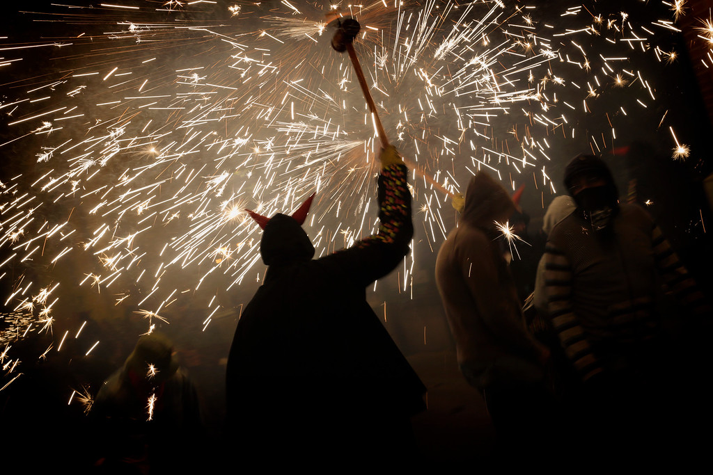 ". Revelers hold fireworks as they take part in a ""Correfoc\"" - Run with Fire - party in Barcelona, Spain, Saturday, May 21, 2016. Correfocs or \""fire-runs\"" originate from a form of medieval street theatre that represents the fight of good against evil through parades using fireworks and effigies of the devil. During the correfoc, a group of individuals dress as devils and light fireworks. While dancing to the drums, they will set off their fireworks among crowds of spectators. (AP Photo/Emilio Morenatti)"