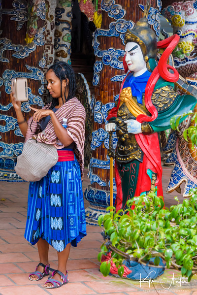 In the courtyard of the Linh Phuoc Pagoda, Lady Buddha observes this young woman checking her text messages.