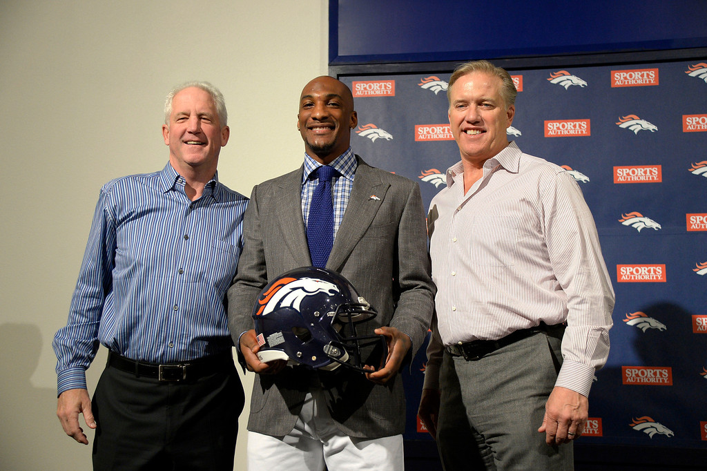 . Denver Broncos head coach John Fox, Aqib Talib and John Elway, General Manager and Executive Vice President of Football Operations pose for a photo after a press conference March 12, 2014 at Dove Valley. (Photo by John Leyba/The Denver Post)