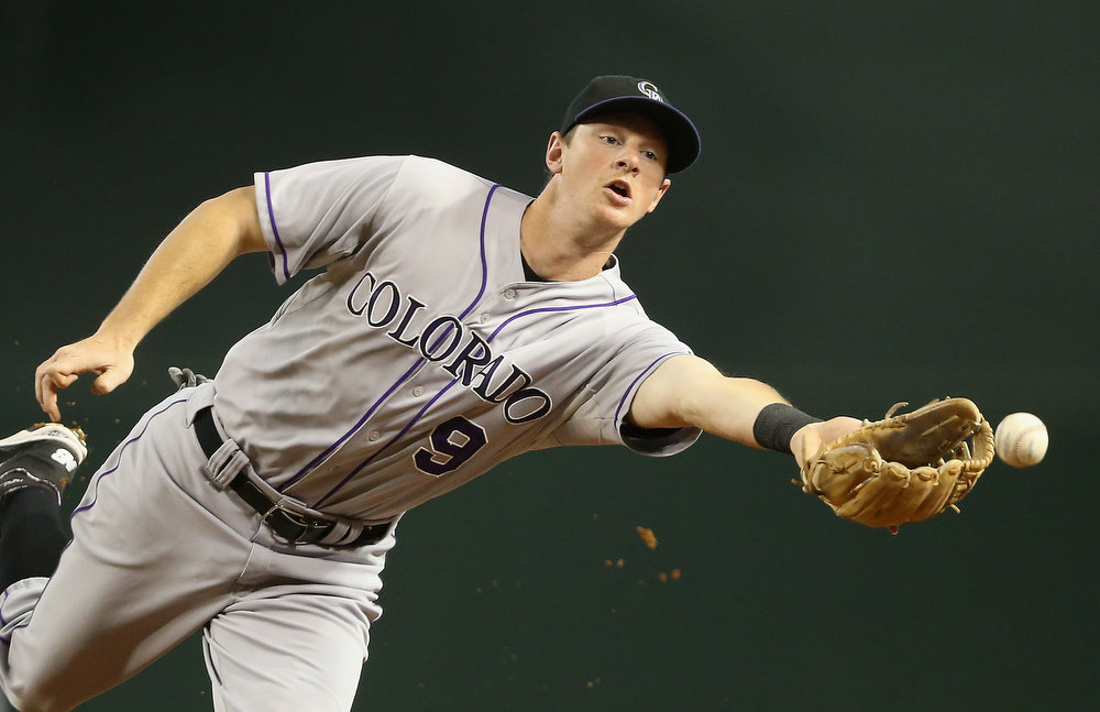 . Infielder DJ LeMahieu #9 of the Colorado Rockies flips the ball to first base for a ground ball out against the Arizona Diamondbacks during the first inning of the MLB game at Chase Field on August 10, 2014 in Phoenix, Arizona.  (Photo by Christian Petersen/Getty Images)