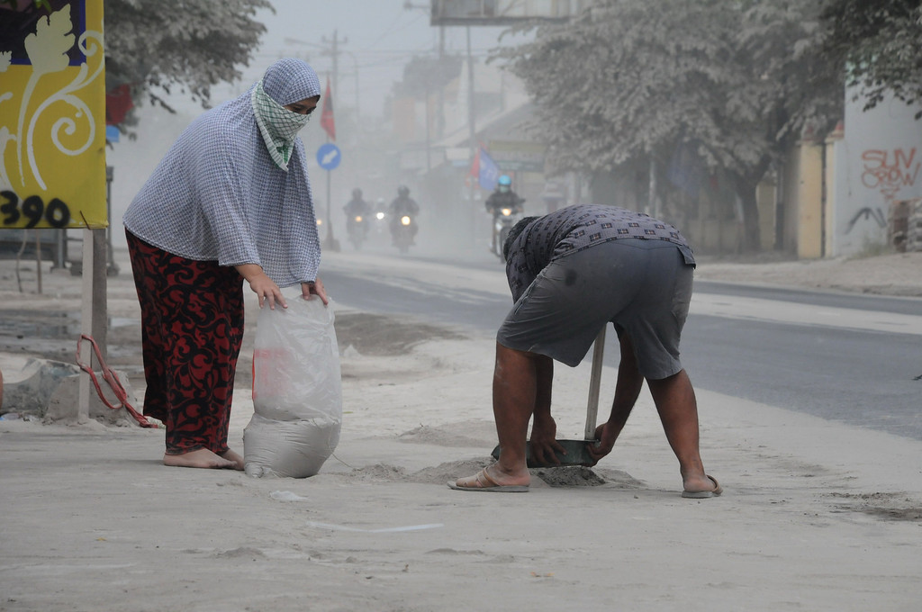 . Residents clean up volcanic ash on their property in Solo in Central Java province on February 14, 2014 following the eruption of Mount Kelud volcano.   AFP PHOTO / ANWAR MUSTAFA/AFP/Getty Images