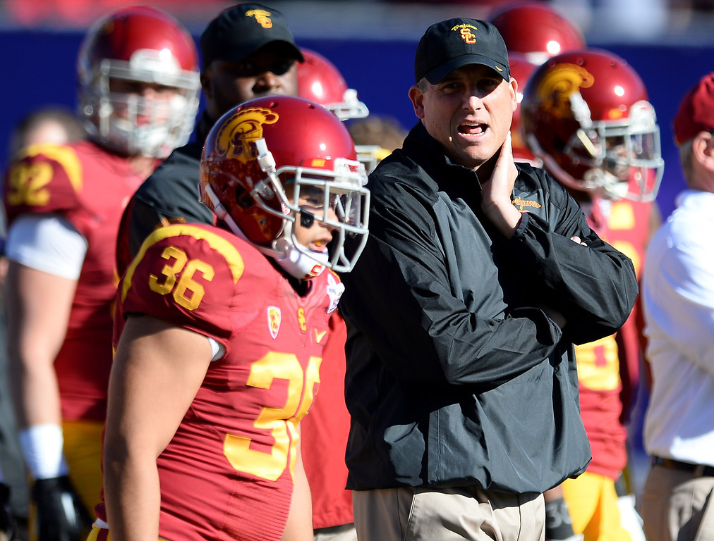 . LAS VEGAS, NV - DECEMBER 21:  Interim coach Clay Helton of the USC Trojans watches his players, including John Akiba #36, warm up before playing the Fresno State Bulldogs in the Royal Purple Las Vegas Bowl at Sam Boyd Stadium on December 21, 2013 in Las Vegas, Nevada. USC won 45-20.  (Photo by Ethan Miller/Getty Images)