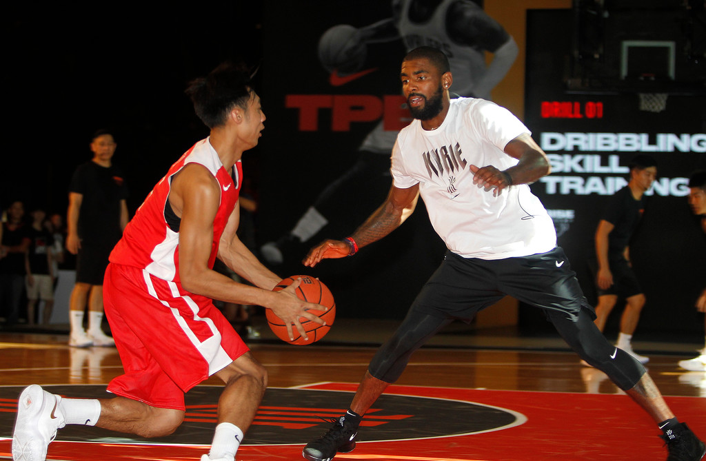. NBA Cleveland Cavaliers guard Kyrie Irving, right, gives instructions while he holds a short basketball clinic with young Taiwanese players in Taipei, Taiwan, Saturday, July 22, 2017. (AP Photo/Chiang Ying-ying)