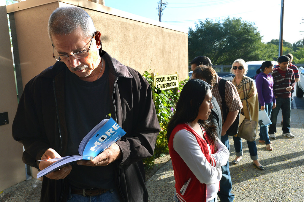 . Eric Moon of Pleasant Hill reads a book as he and others stand in line at the Social Security office in Walnut Creek, which stayed open during the federal government shutdown, in Walnut Creek, Calif., on Tuesday, Oct. 1, 2013. Tuesday was the first day of the federal government shutdown, and many federal offices were closed. (Dan Rosenstrauch/Bay Area News Group)