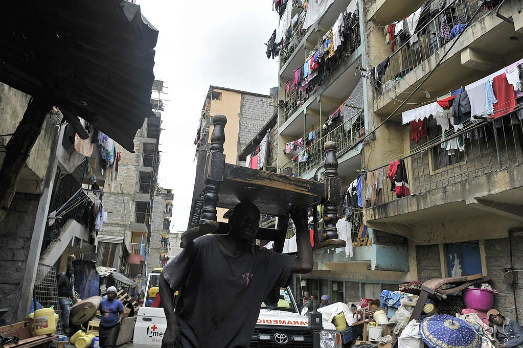 . A man carries a piece of furniture as people leave the vicinity of a collapsed building in Nairobi on April 30, 2016.  / AFP PHOTO / SIMON MAINA/AFP/Getty Images