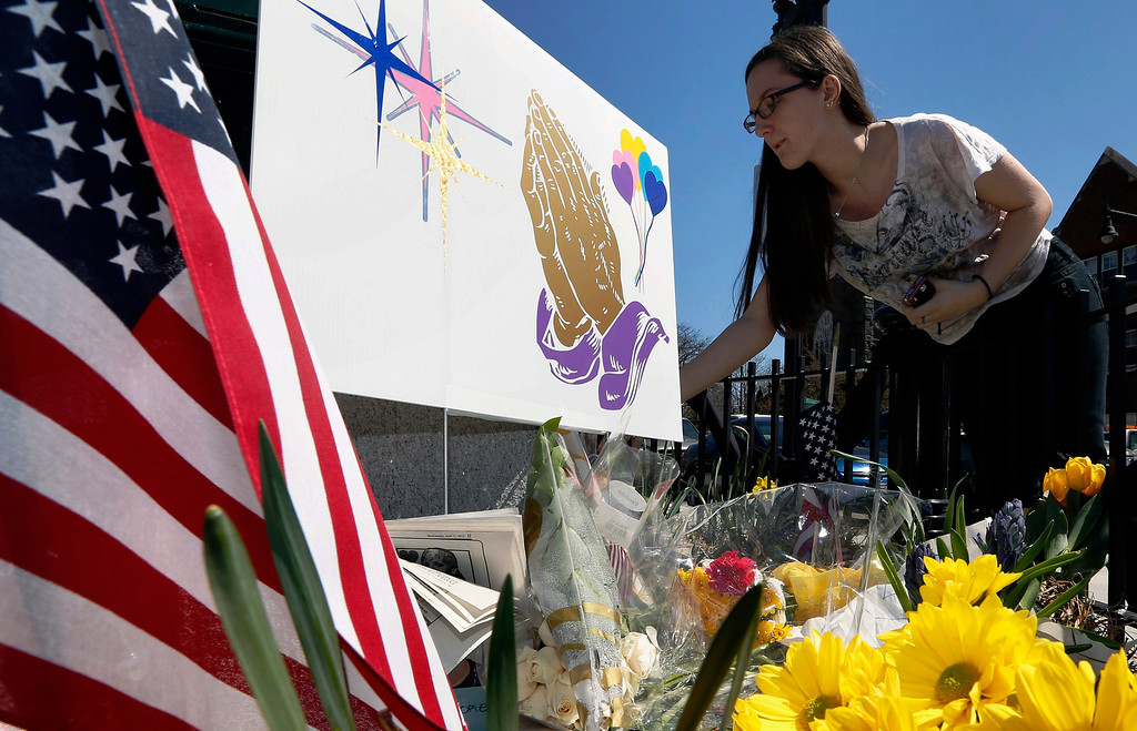 . Shannon Walsh, 15, places flowers on a memorial to Boston Marathon bombing victim, Martin Richard, 8, near the Richard family house in the Dorchester neighborhood of Boston, Wednesday, April 17, 2013. (AP Photo/Michael Dwyer)