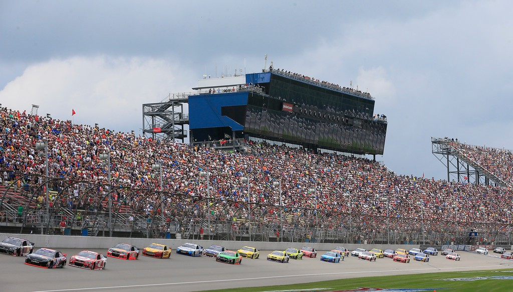 . The field drives by the grandstand at the start of the NASCAR Sprint Cup series auto race at Michigan International Speedway, Sunday, June 14, 2015, in Brooklyn, Mich. (AP Photo/Carlos Osorio)
