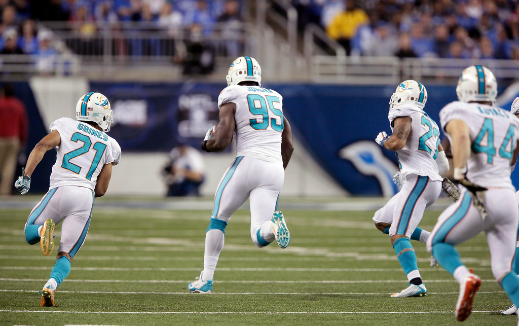 . Miami Dolphins defensive end Dion Jordan (95) returns the ball 58-yards after picking it up after teammate defensive tackle Earl Mitchell (90) blocked a kick by Detroit Lions\' Matt Prater during the second half of an NFL football game in Detroit, Sunday, Nov. 9, 2014. (AP Photo/Duane Burleson)