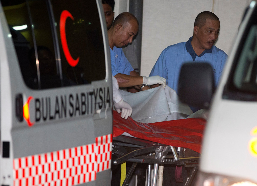 . Hospital staff remove a body from a van outside the Kuala Lumpur General Hospital after a bus carrying tourists and local residents fell into a ravine near the Genting Highlands, about an hour\'s drive from Kuala Lumpur, Malaysia, Wednesday, Aug. 21, 2013. (AP Photo/Mark Baker)