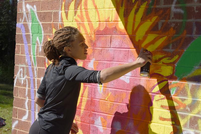 Alpha Kappa Alpha service chair Makaylla Binter, a studio art and biology double major, helped a sunflower bloom on a mural at the Ada Jenkins Center. (Bill Giduz photo)
