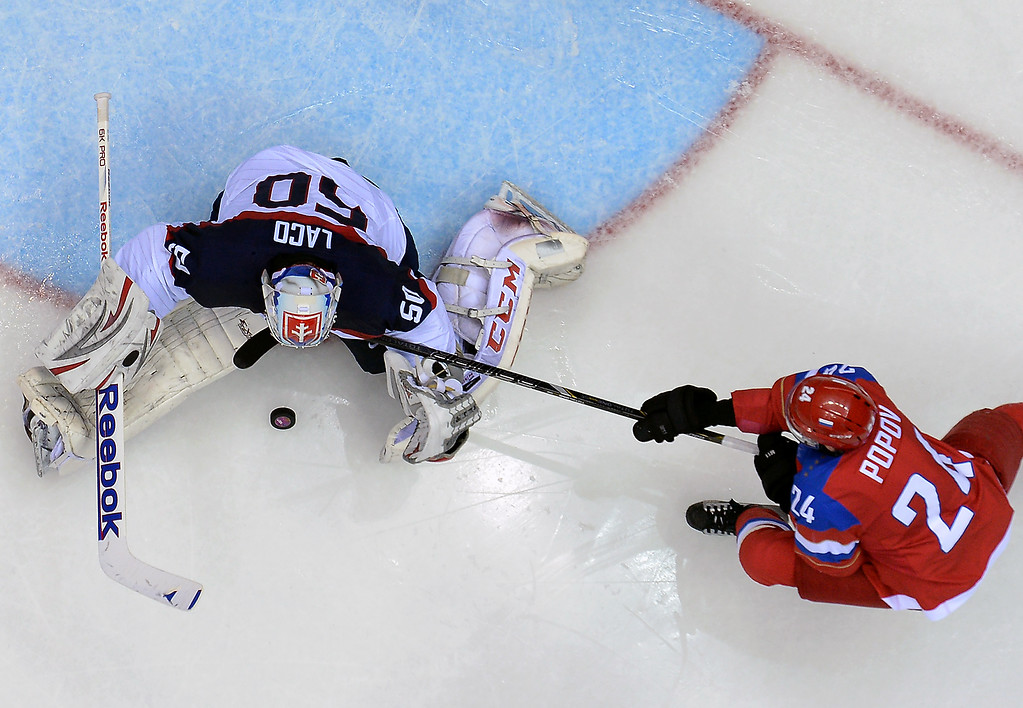 . Russia\'s Alexander Popov (R) challenges Slovakia\'s goalkeeper Jan Laco during the Men\'s Ice Hockey Group A match between Russia and Slovakia at the Bolshoy Ice Dome in Sochi during the Sochi Winter Olympics on February 16, 2014.  ALEXANDER NEMENOV/AFP/Getty Images