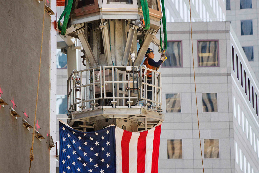 . A worker from Ground Zero attaches straps to the final piece of One World Trade Center\'s spire as it is prepared to be lifted to the top of the building in New York, May 2, 2013.   REUTERS/Lucas Jackson