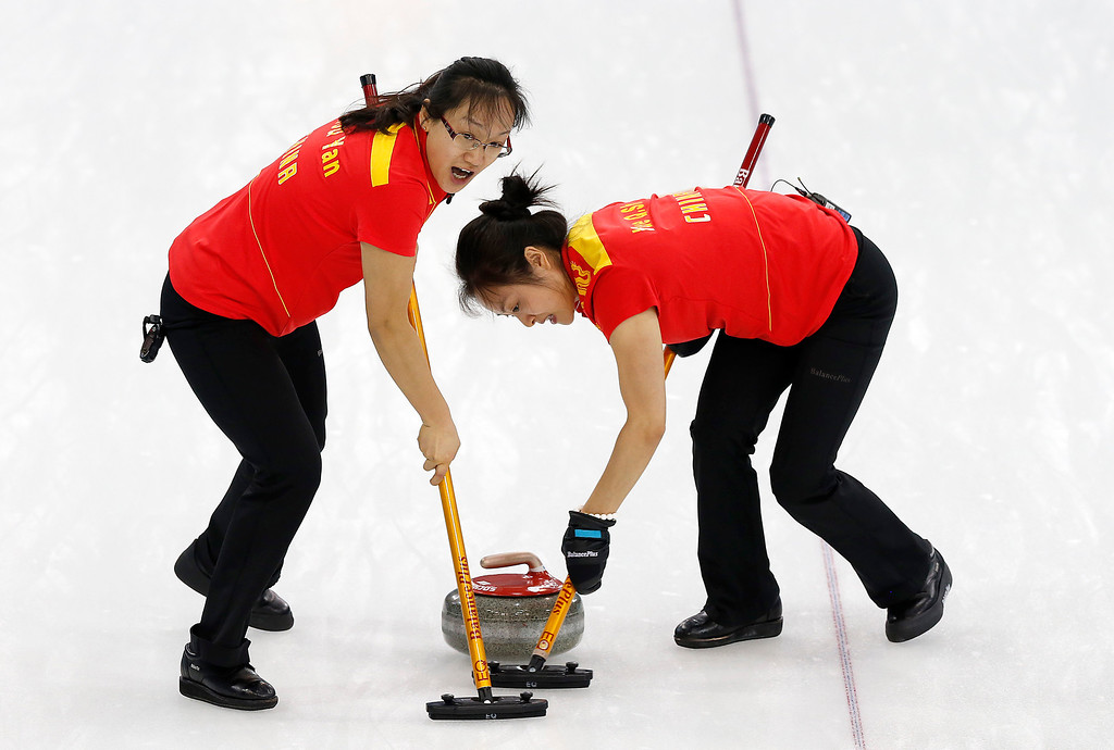 . China\'s Zhou Yan, left, and Yue Qingshuang sweep the ice during the women\'s curling competition against Britain at the 2014 Winter Olympics, Thursday, Feb. 13, 2014, in Sochi, Russia. (AP Photo/Wong Maye-E)
