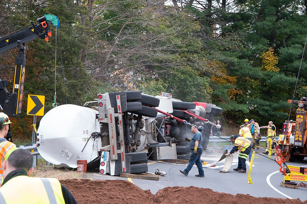 10/29/19 Wesley Bunnell | StaffrrA semi trailer carrying hot asphalt overturned on the Mill St exit in Berlin this morning causing asphalt to spill from the top of the tanker mostly onto a grassy divider. A tow company works on uprighting the trailer.