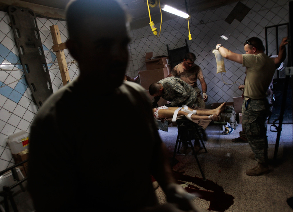 """. An Iraqi Army soldier (L) watches as medics of the Army\'s 2-12 Cavalry Battalion try to save a civilian man injured by a roadside bomb aimed at Iraqi troops by local militants at Joint Security Station Casino in the divided Gazaliyah neighborhood June 29, 2007 in Baghdad, Iraq.  Gazaliyah, one of Baghdad\'s most troubled neighborhoods, is patrolled by the 2-12 Cavalry out of Joint Security Station Casino, one of the field bases that figures prominently in the \""""surge\"""" strategy of General David Petraeus.  (Photo by Chris Hondros/Getty Images)"""