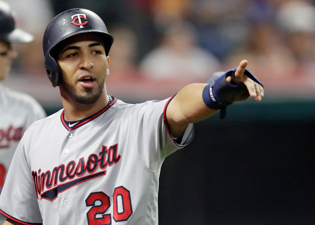 . Minnesota Twins\' Eddie Rosario points to Robbie Grossman after Grossman hit a two-run single in the seventh inning of a baseball game against the Cleveland Indians, Wednesday, Aug. 29, 2018, in Cleveland. Rosario scored on the play. (AP Photo/Tony Dejak)