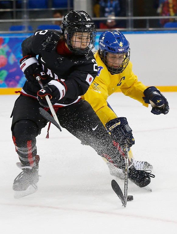 . Shiori Koike of Japan and Jenni Asserholt of Sweden battle for control of the puck during the third period of the 2014 Winter Olympics women\'s ice hockey game at Shayba Arena, Sunday, Feb. 9, 2014, in Sochi, Russia. (AP Photo/Petr David Josek)