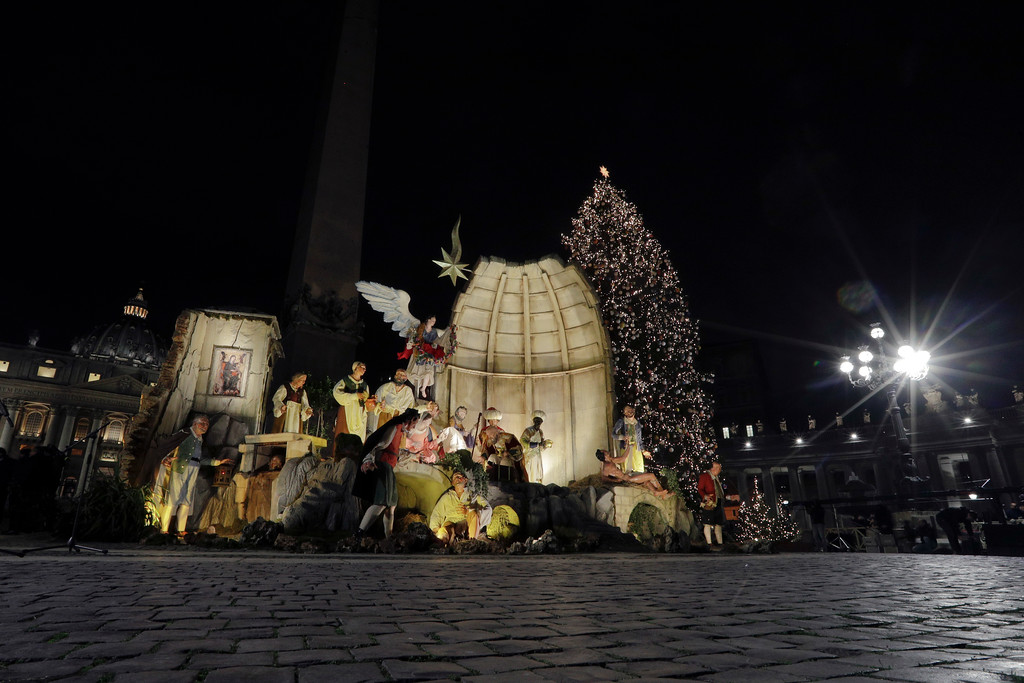 . The 21 meters (69 feet) high Christmas tree coming from Poland and a Nativity Scene are backdropped by St. Peter\'s Basilica after being lit in St. Peter\'s Square at the Vatican, Thursday, Dec. 7, 2017. (AP Photo/Andrew Medichini)