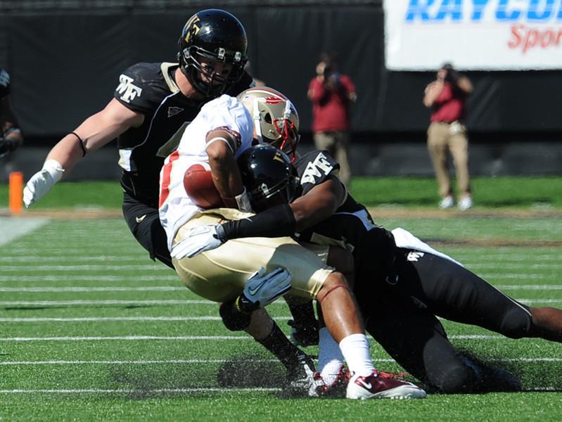 Josh Bush and Mike Olson tackle Rashad Greene.jpg