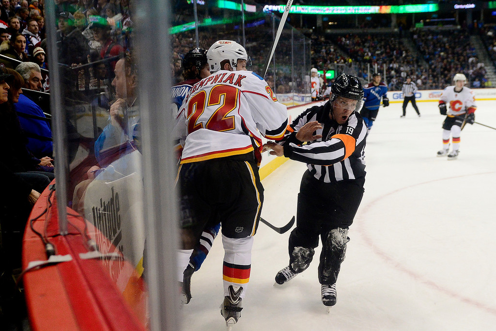 . A referee catches his breathe after nearly being wiped out by Lee Stempniak (22) of the Calgary Flames and Nathan MacKinnon (29) of the Colorado Avalanche during the first period.   (Photo by AAron Ontiveroz/The Denver Post)