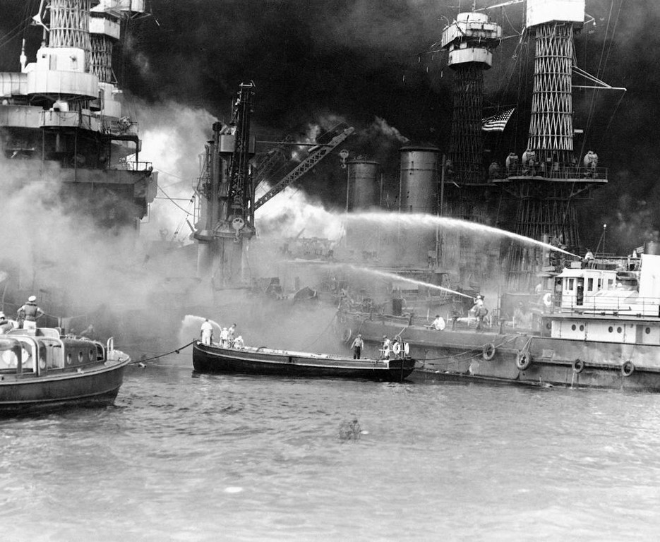 . In this image provided by the U.S. Navy, U.S. sailors man boats at the side of the blazing USS West Virginia to fight the flames started by Japanese torpedoes and bombs on the battleship at Pearl Harbor, Hawaii on Dec. 7, 1941. The Stars and Stripes fly bright against the smoke-blackened sky over the harbor. (AP Photo/U.S. Navy)