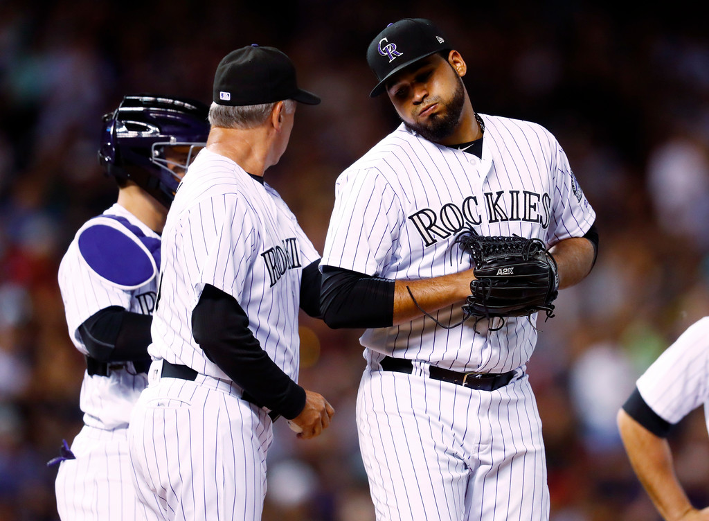 . Colorado Rockies manager Bud Black, center, pulls starting pitcher Antonio Senzatela, right, from the mound as catcher Tony Wolters looks on after Senzatela gave up a single to Cleveland Indians\' Yan Gomes in the seventh inning of an interleague baseball game Tuesday, June 6, 2017, in Denver. The Rockies won 11-3. (AP Photo/David Zalubowski)