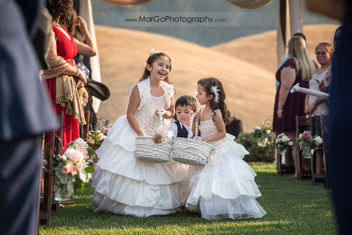 flower girls walking down the aisle during wedding ceremony at Taber Ranch Vineyards