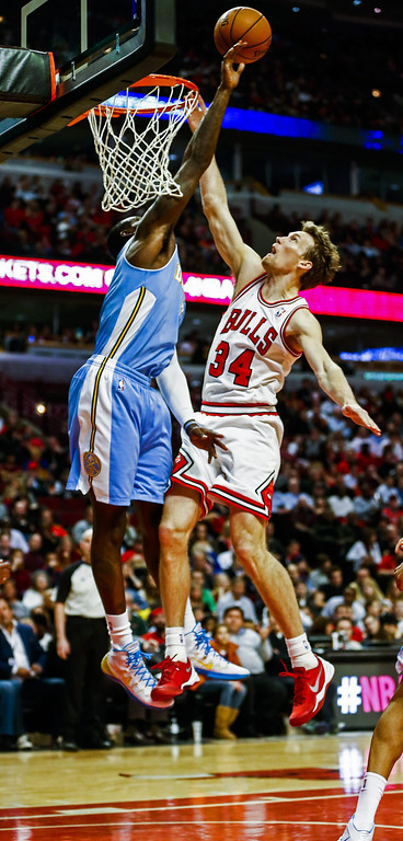 . Denver Nuggets center J.J. Hickson (L) attempts to block a shot by Chicago Bulls forward Mike Dunleavy (R) in the second half of their NBA game at the United Center in Chicago, Illinois, USA, 21 February 2014. The Bulls defeated the Nuggets.  EPA/TANNEN MAURY