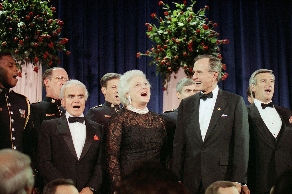 """. President George H.W. Bush, second from right, and first lady Barbara Bush, second from left, joined by Jack Valuate, left, president of the Motion Picture Association of America and Gene Jankowski the new chairman of the American Film Institute, in singing \""""God Bless America\"""", Sept. 27, 1983, in Washington, D.C. The president and first lady were on hand for the star-studded, 25th anniversary of the American Film Institute. (AP Photo/Dennis Cook)"""