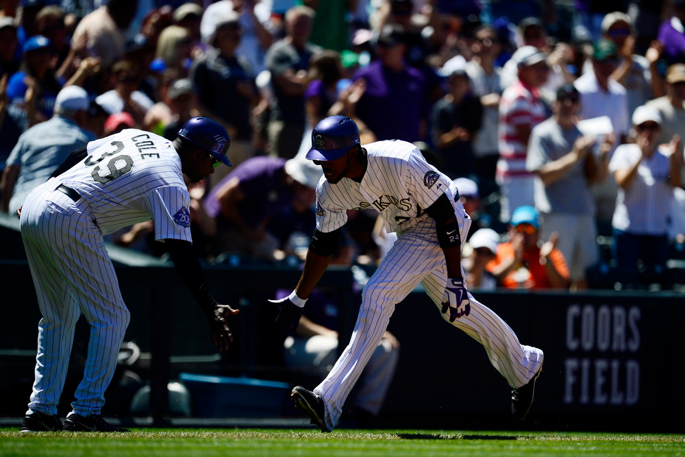 . Colorado Rockies third base coach Stu Cole (39) low-fives center fielder Dexter Fowler (24) after he hit a first inning home run off of Los Angeles Dodgers starting pitcher Matt Magill (36) during action in Denver. The Colorado Rockies hosted the Los Angeles Dodgers at Coors Field. (Photo by AAron Ontiveroz/The Denver Post)