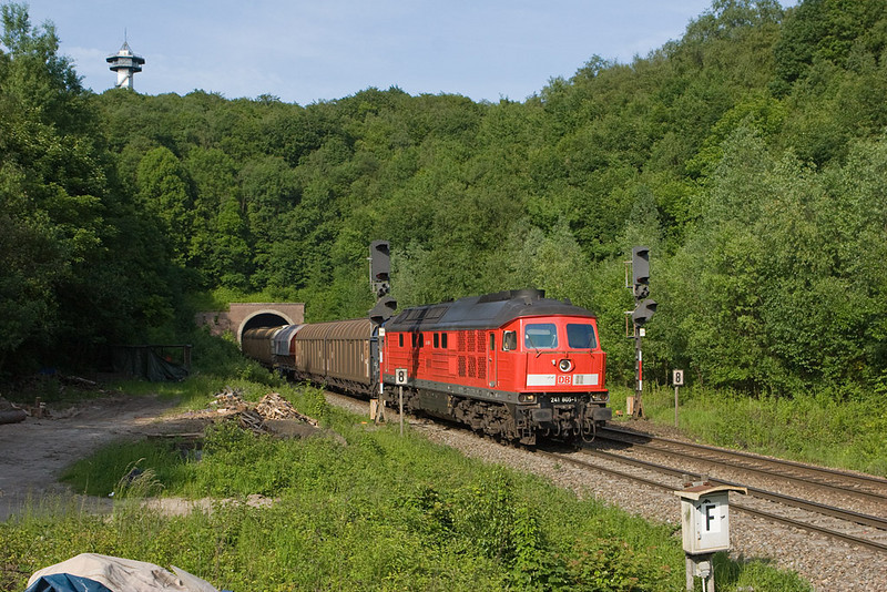 241 805 brings a freight westbound out of the tunnel at Gemmenich. The tower up top sits at the point where the Netherlands, Belgium, and Germany adjoin. The train has crossed from Germany into Belgium while inside the tunnel. The dirt road at left is part of the old original 1870 alignment of the railway line between Aachen/D and Welkenraedt via Plombieres.