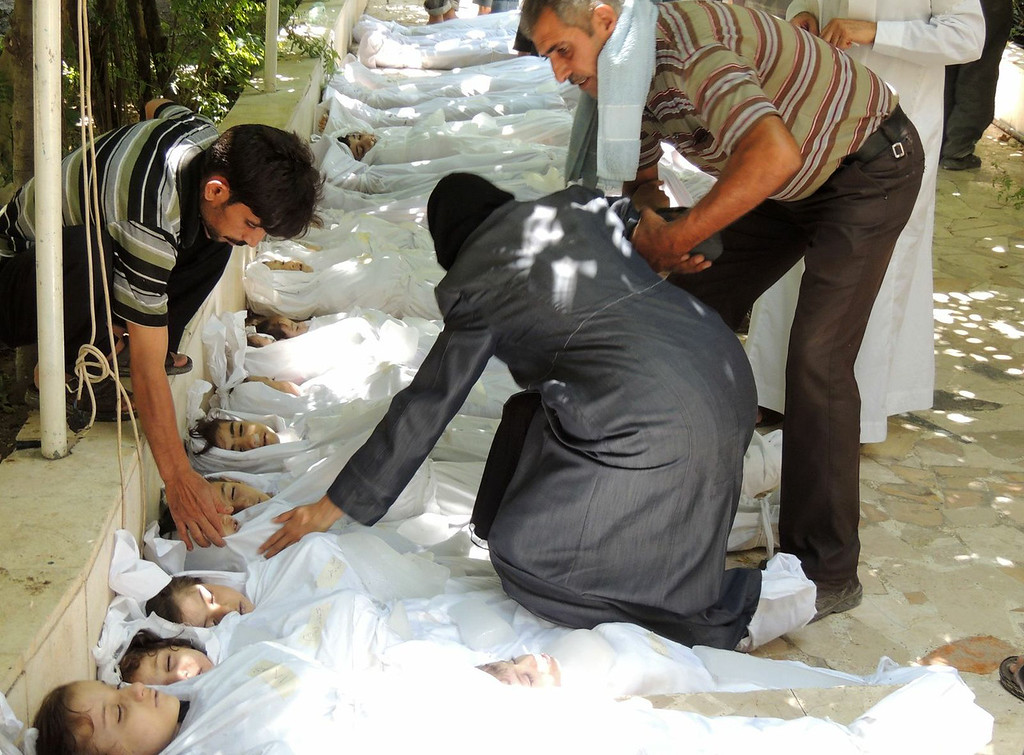 . A handout image released by the Syrian opposition\'s Shaam News Network shows a woman mourning over a body wrapped in shrouds laid out in a line on the ground with other victims which Syrian rebels claim were killed in a toxic gas attack by pro-government forces in eastern Ghouta, on the outskirts of Damascus on August 21, 2013. The allegation of chemical weapons being used in the heavily-populated areas came on the second day of a mission to Syria by UN inspectors, but the claim, which could not be independently verified, was vehemently denied by the Syrian authorities, who said it was intended to hinder the mission of UN chemical weapons inspectors. DAYA Al-DEEN/AFP/Getty Images