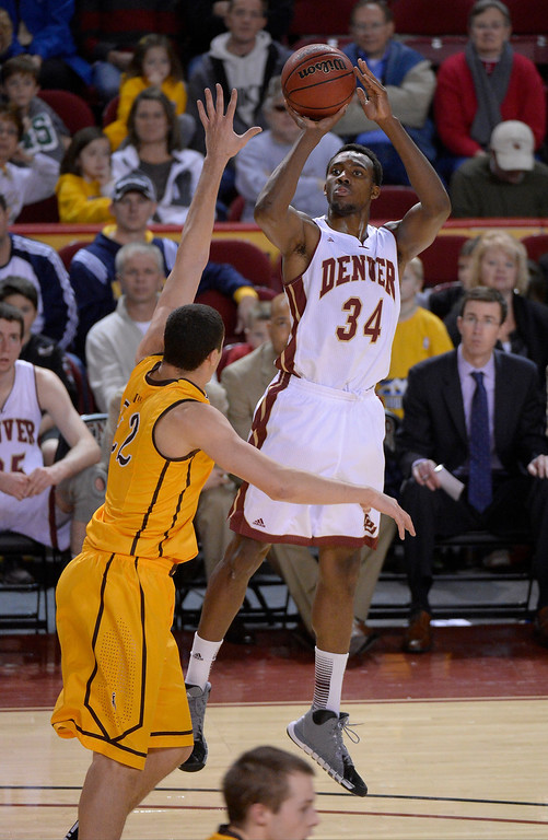 . Denver Pioneers forward Chris Udofia (34) takes a shot over Wyoming Cowboys forward Larry Nance Jr. (22) during the second half December 15, 2013 Magness Arena. The ,pioneers defeated the Cowboys 64-61. (Photo by John Leyba/The Denver Post)