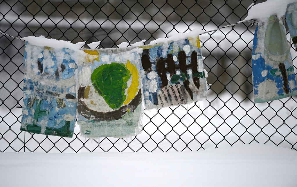 . Children\'s paintings hang on a fence at the Stapleton Greenway Garden near 23rd Ave and Spruce St. in Denver, Tuesday morning, April 16th, 2013 in a fresh blanket of snow. Andy Cross, The Denver Post