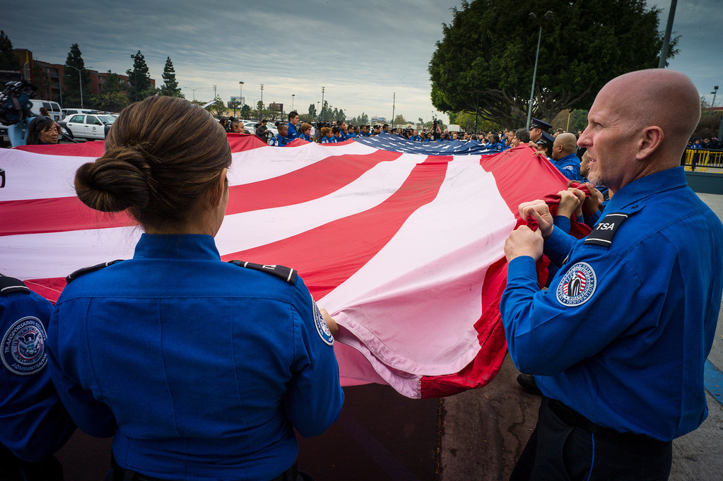 . TSA officers fold a giant US flag at the memorial for slain TSA officer Gerardo Hernandez at the Los Angeles Sports Arena Tuesday, November 12, 2013.  A public memorial was held for Officer Gerardo who was killed at LAX when a gunman entered terminal 3 and opened fire with a semi-automatic rifle.  ( Photo by David Crane/Los Angeles Daily News )