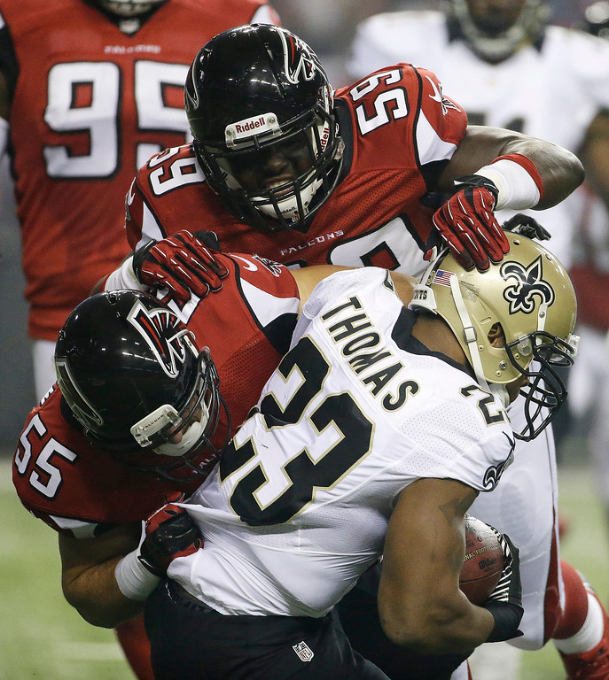 . New Orleans Saints running back Pierre Thomas (23) is hit by Atlanta Falcons outside linebacker Joplo Bartu (59) and Atlanta Falcons outside linebacker Paul Worrilow (55) during the first half of an NFL football game, Thursday, Nov. 21, 2013, in Atlanta. (AP Photo/David Goldman)