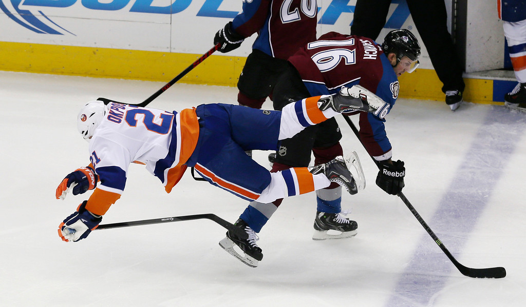 . New York Islanders right wing Kyle Okposo, left, falls after being tripped up by Colorado Avalanche defenseman Cory Sarich during the second period of an NHL hockey game in Denver on Friday, Jan. 10, 2014. (AP Photo/David Zalubowski)