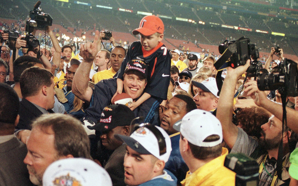 . John Elway carries his son, Jack, on his shoulders a after the Denver Broncos won Super Bowl XXXII against the Green Bay  Packers.   (Karl Gehring/The Denver Post)