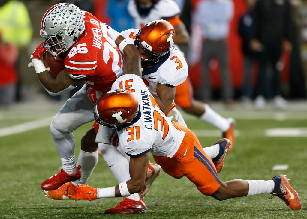 . Ohio State running back Mike Weber, left, runs through the line of scrimmage as Illinois defenders Del\'Shawn Phillips, right, and Cameron Watkins make a tackle during the first half of an NCAA college football game Saturday, Nov. 18, 2017, in Columbus, Ohio. (AP Photo/Jay LaPrete)
